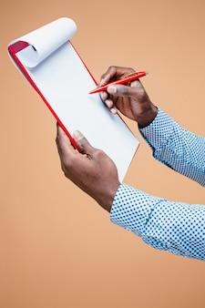 Mannelijke hand die op leeg geïsoleerd klembord schrijft ,.