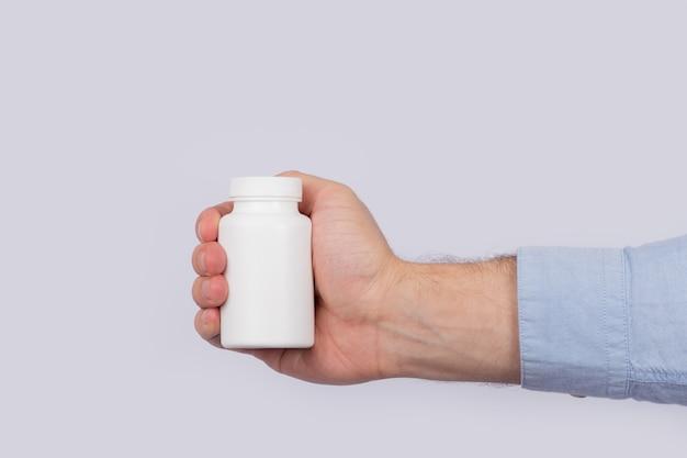 Mannelijke hand die plastic fles pillen houdt. detailopname. kopieer ruimte. sjabloon. mockup
