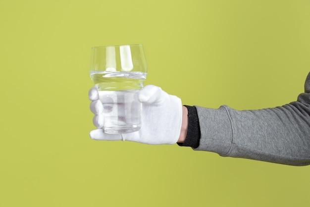 Mannelijke hand die witte beschermende handschoen draagt die glas zuiver water houdt dat op gele muur wordt geïsoleerd.
