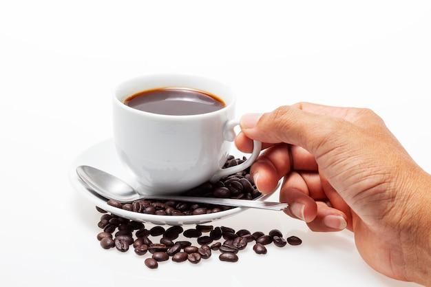 Mannelijke hand die witte koffiekop en koffiebonen op wit houdt
