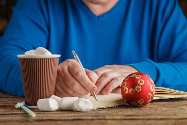Mannelijke hand het schrijven plannen voor nieuw jaar in notitieboekje terwijl aangezien hij hete chicolate drinkt