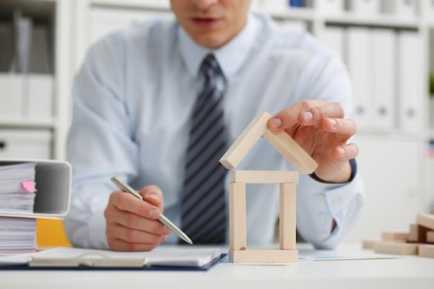 Mannelijke hand houdt het dak van speelgoed huis