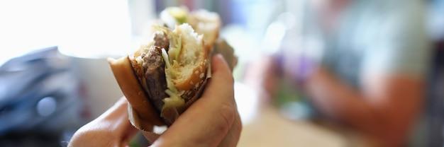 Mannelijke hand houdt teasty hamburger in hand tegen