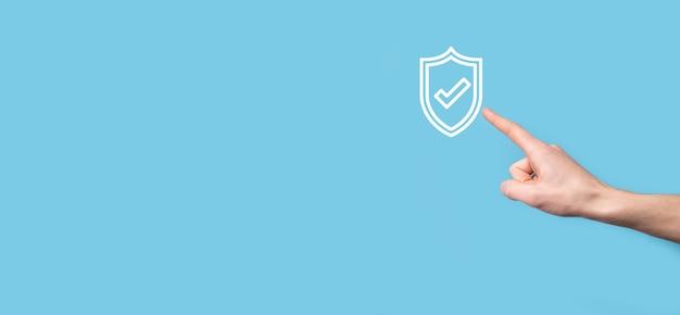 Mannelijke hand met beschermen schild met een vinkje op blauwe achtergrond. beveiligingsnetwerkbeveiligingscomputer en veilig uw gegevensconcept.