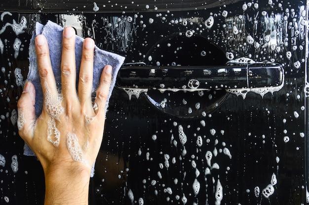 Mannelijke hand met blauwe doek die een auto wassen