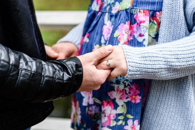 Mannelijke hand met de hand van zijn zwangere vrouw. zwangere vrouw die buik koestert.