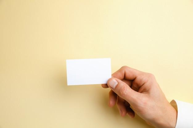 Mannelijke hand met een blanco visitekaartje op zacht geel