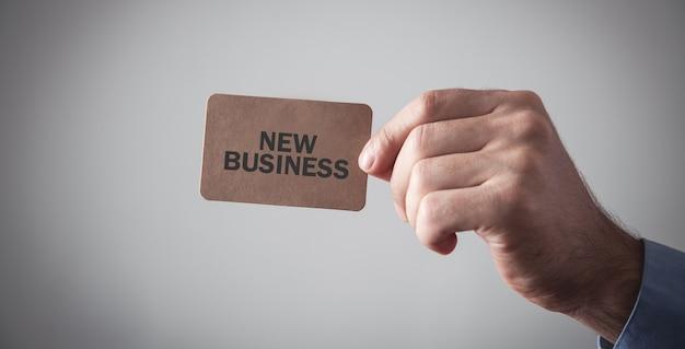 Mannelijke hand met een bruin visitekaartje. nieuwe zaken