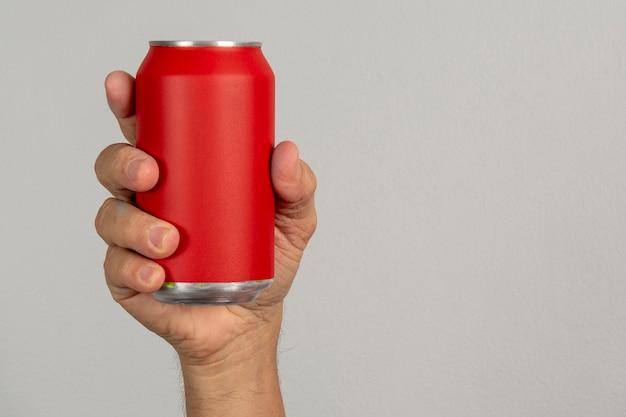 Mannelijke hand met een rood blikje op een grijze achtergrond