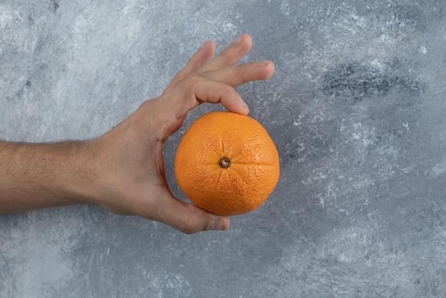 Mannelijke hand met enkele sinaasappel op marmeren tafel.