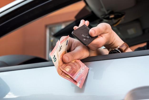 Mannelijke hand met eurorekeningen en sleutel in auto te koop of te huur. financiën
