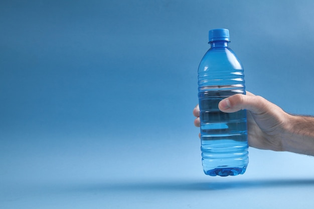 Mannelijke hand met fles water op blauwe achtergrond.