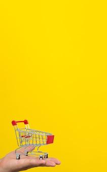 Mannelijke hand met kleine winkelwagen trolley op gele achtergrond.