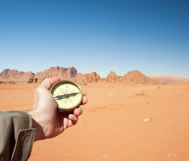 Mannelijke hand met kompas in de woestijn