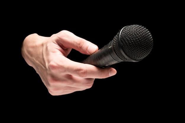 Mannelijke hand met microfoon op een zwarte achtergrond.