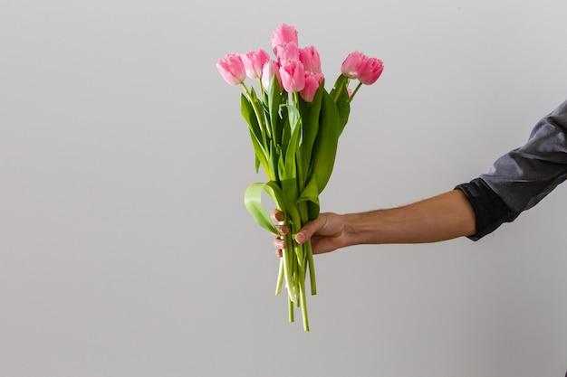 Mannelijke hand met mooie tulpen op witte achtergrond
