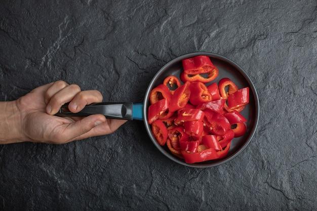 Mannelijke hand met pan van gesneden rode paprika op zwarte achtergrond