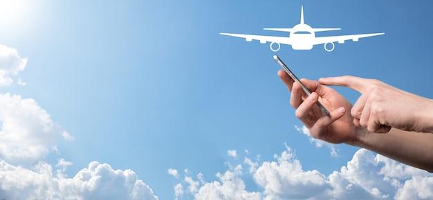 Mannelijke hand met vliegtuig vliegtuigpictogram op blauwe achtergrond. banner.nline ticketaankoop.reispictogrammen over reisplanning, vervoer, hotel, vlucht en paspoort.vliegticket boekingsconcept.