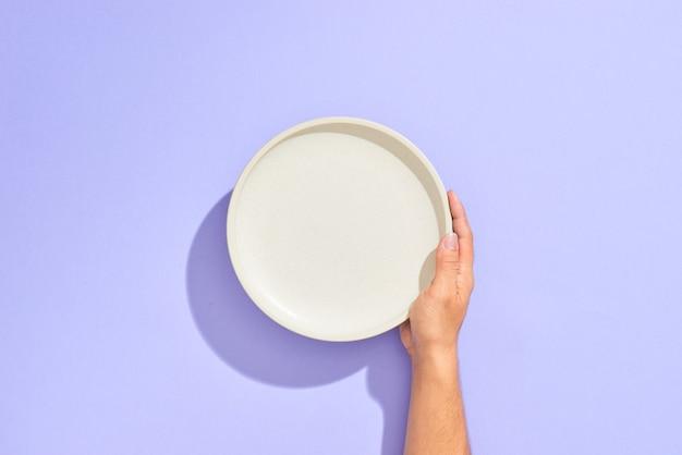 Mannelijke hand met witte plaat, geïsoleerd op lila
