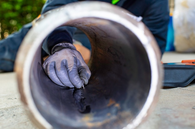 Mannelijke hand werknemer inspectie ultrasone dikte pijp staal materiaal veroorzaakt door roest oude verroeste ijzeren achtergrond concepten, mannenhand close-up kopiëren gebied