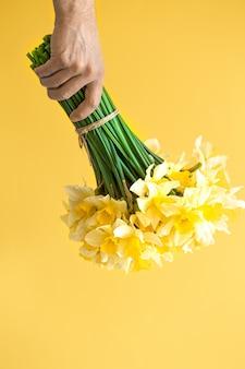 Mannelijke handen als achtergrond met een boeket van bloemen.