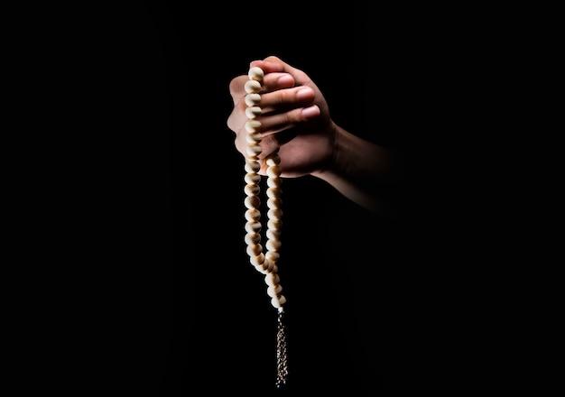 Mannelijke handen bidden met behulp van gebed kralen