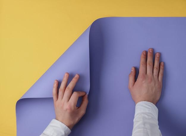 Mannelijke handen buigen een vel gekleurd papier gele achtergrond, kopieer ruimte. bovenaanzicht