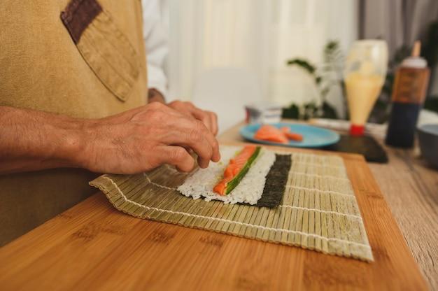Mannelijke handen close-up rollende sushi rollen met bamboe mat