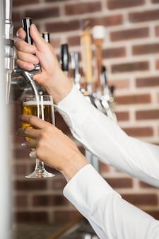 Mannelijke handen die bier gieten