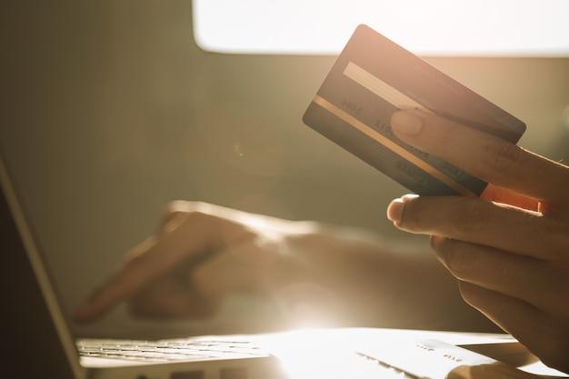 Mannelijke handen die creditcard houden en laptop computer met behulp van