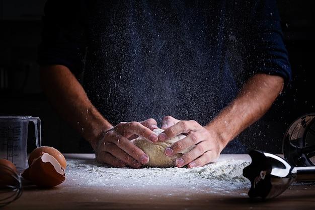 Mannelijke handen die deeg voor pizza, bollen of brood maken. bakken concept.