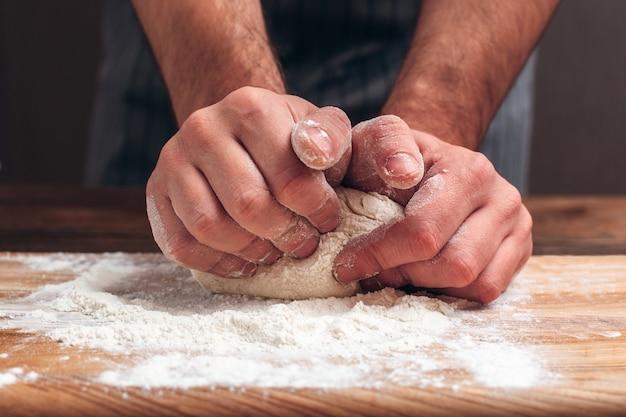 Mannelijke handen die deegclose-up kneden