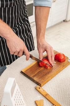 Mannelijke handen die een heerlijke tomaat snijden