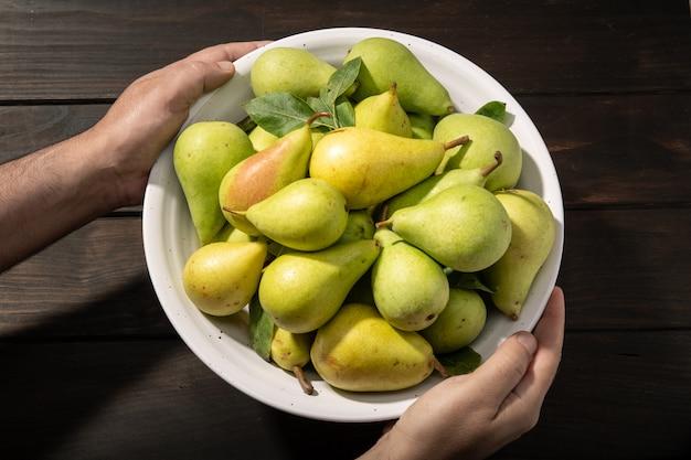 Mannelijke handen die een kom met organische peren houden
