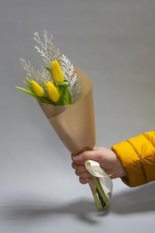 Mannelijke handen die een minimalistisch de lenteboeket van ongebloeide gele tulpen houden en conferen, selectieve nadruk