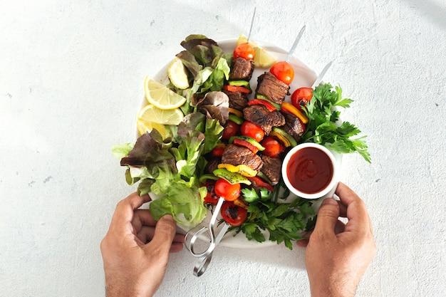 Mannelijke handen die een plaat met rundvlees geroosterde vleeskebab houden met groenten en saus hoogste mening