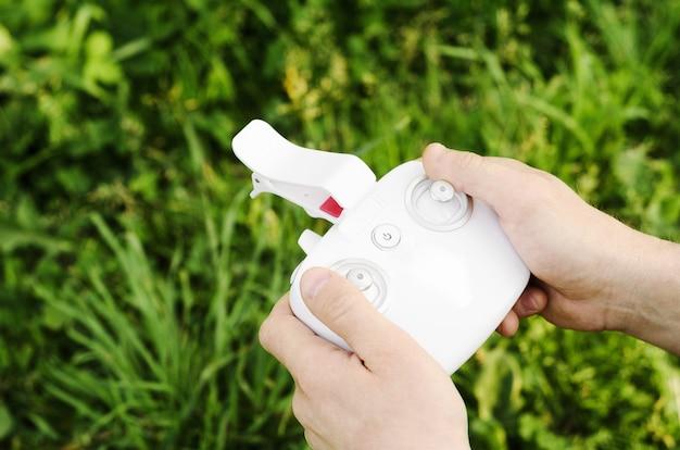 Mannelijke handen die een quadrocopter ver op a van gras houden.