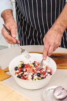 Mannelijke handen die een smakelijke salade mengen