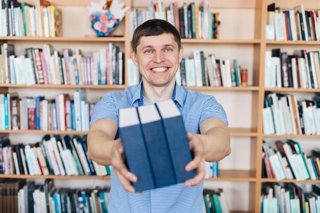 Mannelijke handen die een stapel boeken houden. de mens houdt een stapel boeken stand