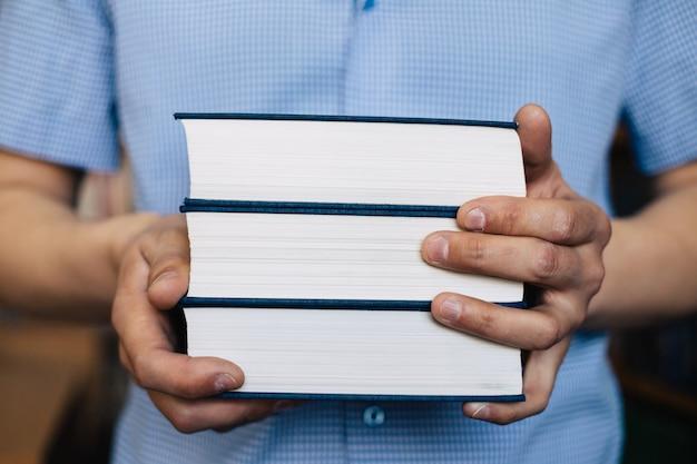 Mannelijke handen die een stapel boeken houden.