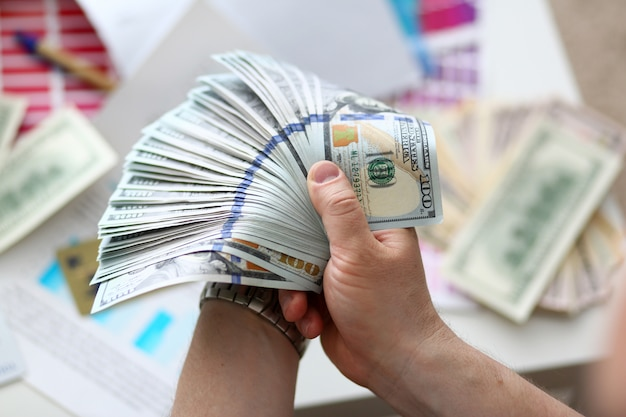 Mannelijke handen die geld van reusachtig pak tellen