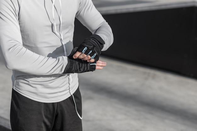 Mannelijke handen die handschoenen voor training zetten