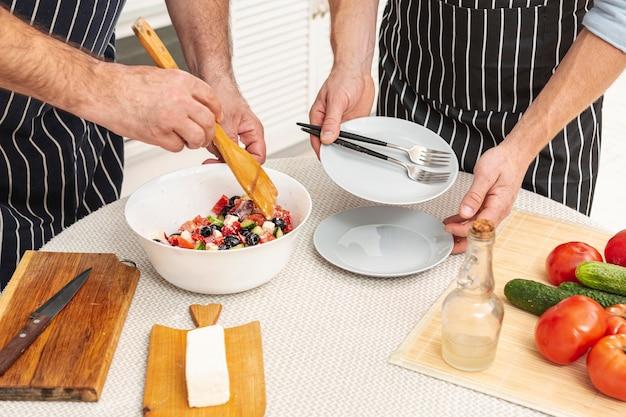 Mannelijke handen die heerlijke salade voorbereiden