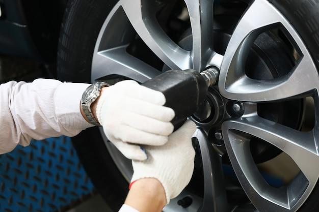 Mannelijke handen die luchtkanon voor autowiel houden