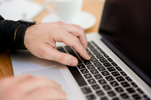Mannelijke handen die op laptop toetsenbord typen. knip uitzicht. moderne gadgets. detailopname. grijze laptop. wazig kopje koffie op de achtergrond. mens in zwart overhemd. mannelijke freelancer die vanuit café werkt.