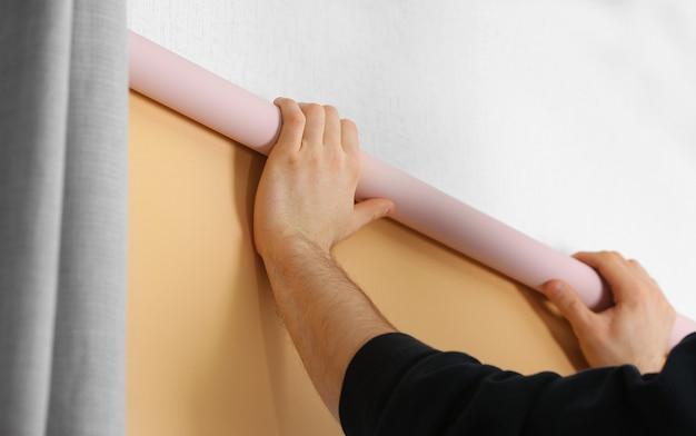 Mannelijke handen die rolgordijnen op venster installeren