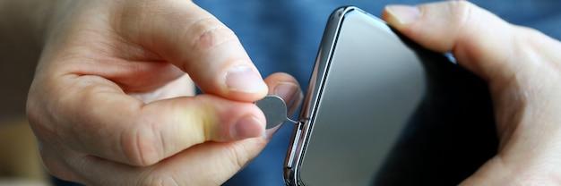 Mannelijke handen die simkaartgroef van zijn smartphone uit close-up krijgen