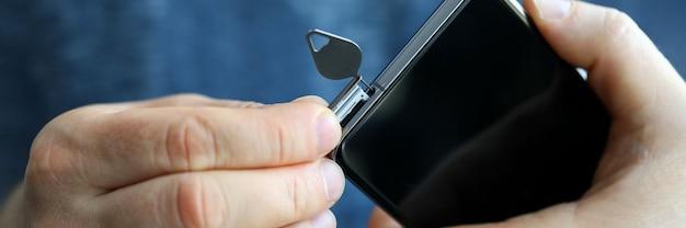 Mannelijke handen die simkaartgroef van zijn smartphone weggaan