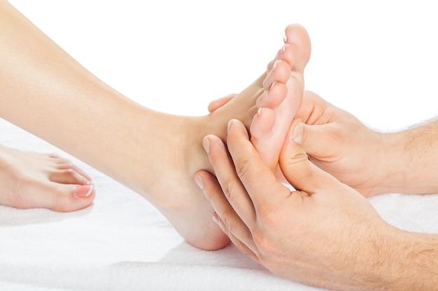 Mannelijke handen die voet masseren