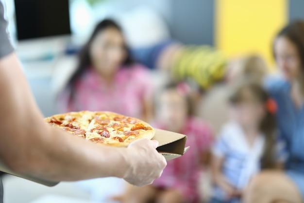 Mannelijke handen dragen pizza op kartonnen standaard. op de achtergrond zitten twee vrouwen en twee kinderen op de bank